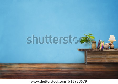 green plants pottery vase on drawer wooden in empty blue vintage living room interior #518923579