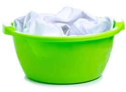 Green plastic bowl with laundry clothes on white background isolation