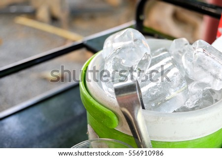 green plastic bucket with ice cubes