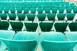 Green plastic chair rows in a cricket stadium for audience to sit on. These plastic seats are for audiences and are shown empty here before a match