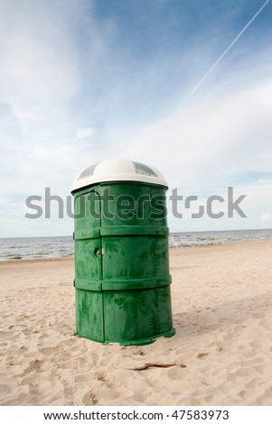 Green plastic portable toilet in the sandy beach