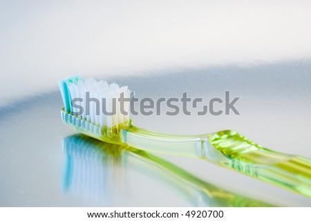 Green plastic toothbrush reflected on metallic surface.