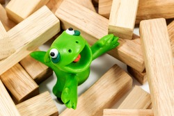 Green plasticine creature looking up standing on a block of wood