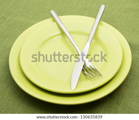 Green plates with fork and knife