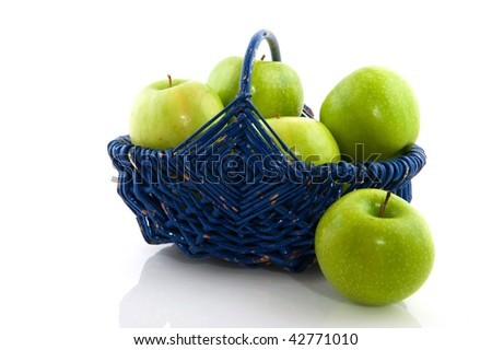 Green plucked apples in a blue basket