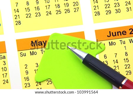 Green post it and pen on calendar