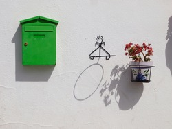 Green postbox hung on the wall next to a flower pot