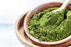 Green powder chlorella, spirulina on gray concrete background. Concept dieting, detox, healthy superfood, which contains protein. Copy space.