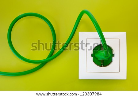 Green power plug into white power outlet against an olive green background - stock photo