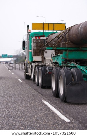 Green powerful American Big rig semi truck with long open flat bed semi trailer transporting oversized metal pipe cargo fortified with chain stretches on the straight highway #1037321680