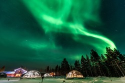 Green powerful bright aurora above igloo house in Finland