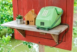 Green public coin phone In the countryside With a tree and nature background
