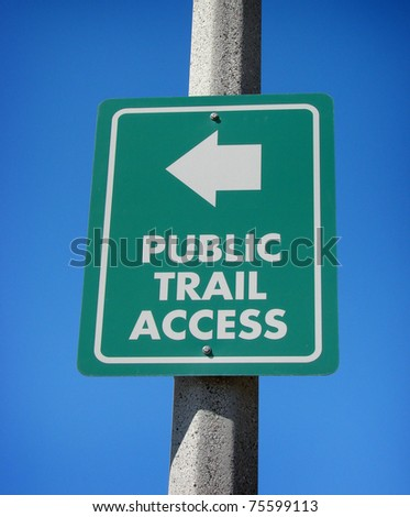 green public trail access sign with arrow and blue sky