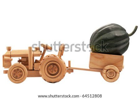Green pumpkin in wooden toy tractor cart, isolated on white background.