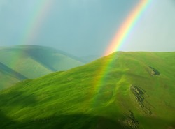 Green pure beauty of Alpine meadows. Belt of mountain meadows above 3 thousand meters above sea level and a high-altitude double rainbow (second-order rainbow)