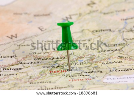 Green pushpin marking a location on a map