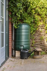 Green rain barrel and a watering can to collect rainwater and reusing it to water the paints and flowers in a backyard with a wattle fence made of willow branches on a sunny day