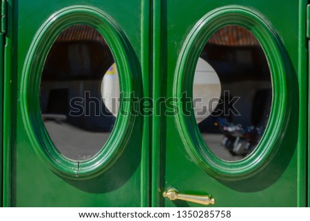 Green rear doors with oval windows of an old car  #1350285758