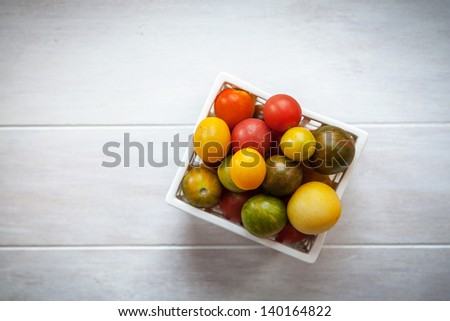 Green, red and yellow Heirloom tomatoes in a white container on a white good background with a light vignette