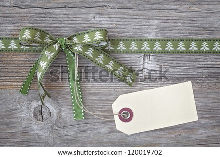 Green ribbon with a tag on wooden background