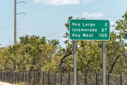 Green road sign for Key Largo, Islamorada and Key west island along Overseas highway in Florida isolated on street