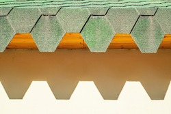 Green roof with hexagonal tiles. Roof with jagged edges casting hard shadows on the wall.