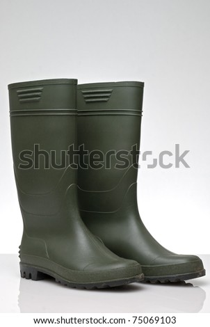 Green rubber boots isolated on white background.