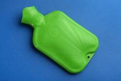 Green rubber hot water bottle on blue background, top view