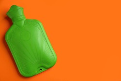Green rubber hot water bottle on orange background, top view. Space for text