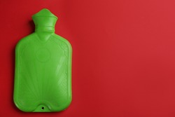 Green rubber hot water bottle on red background, top view. Space for text