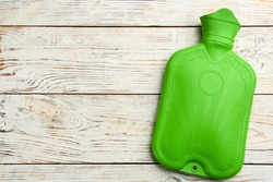 Green rubber hot water bottle on white wooden background, top view. Space for text