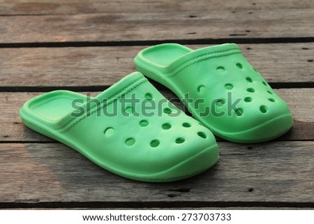 Green rubber slippers on old wooden floor.