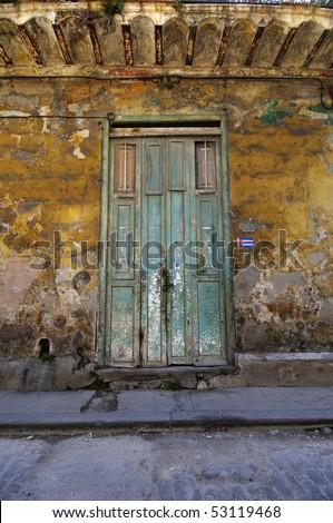 Green rustic door over crumbling walls in eroded building facade in Old Havana, Cuba.