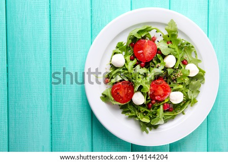 Green salad made with  arugula, tomatoes, cheese mozzarella balls and sesame  on plate, on color wooden background