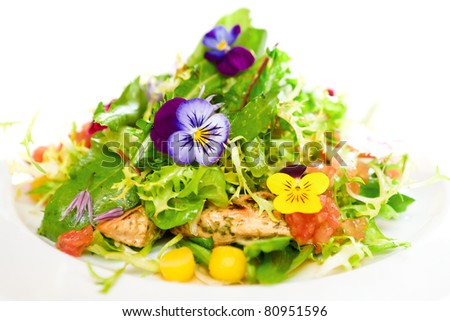 Green salad on a white plate with flowers, meat, corn and tomatoes.