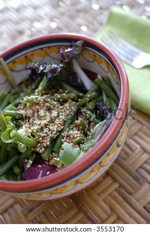 Green salad with green beans and sesame seeds on rattan surface.