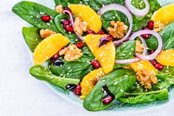 Green salad with spinach and orange, nuts.Healthy detox food plate.
