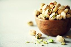 Green salted pistachios in wooden bowls on light concrete background. Copy space for your text. Healthy nuts snack.
