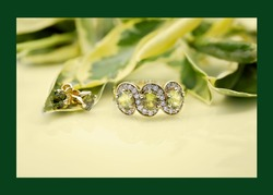 Green sapphire and diamond ring with matching sapphire and gold earrings on a dark green background