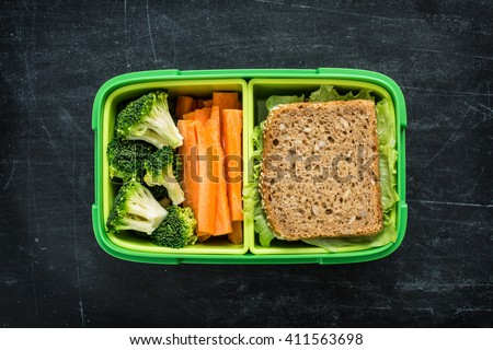 Green school lunch box with sandwich, broccoli and carrot close up on black chalkboard background. Healthy eating habits concept. Flat lay composition (from above, top view).