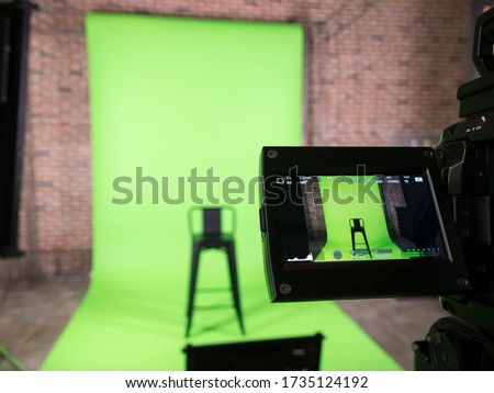 Photo of  green screen backdrop and black chair with lcd display screen on a High Definition TV camera ,  in studio at TV station. Checking before on air.