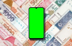 Green screen cell mobile phone on multiple Pakistani Rupees Bank currency notes
