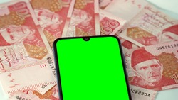 Green screen cell mobile phone with multiple one hundred 100 Rupees Pakistani Bank currency notes