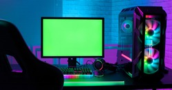 Green screen monitor with powerful personal computer for e cyber sport gamer on the table at home