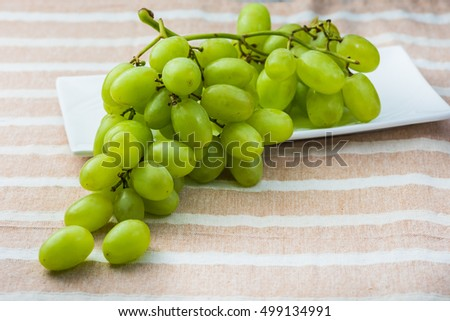 Green seedless grape bunch on ceramic plate and table. #499134991