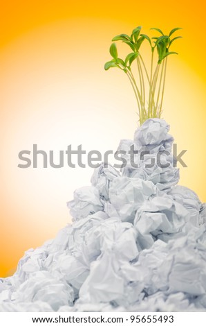 Green seedlings growing out of paper