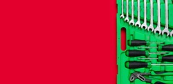 Green set of construction tools: wrenches, adjustable pliers, screwdrivers and so on on a red background. Banner with place for text for a hardware store. Metal hardware for professional repair or DIY