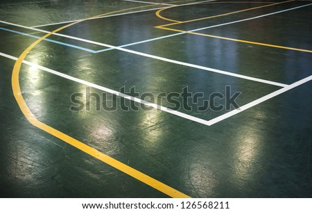 Green shining floor of sports hall with marking lines