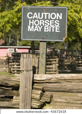 Green sign cautioning that horses may bite atop a wooden fence. Toronto Island, Ontario, Canada.
