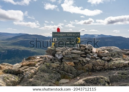 Green sign post with yellow arrows shows directions for the path on the top of the Lomseggen hill in Lom Norway. Summer. Stock fotó ©